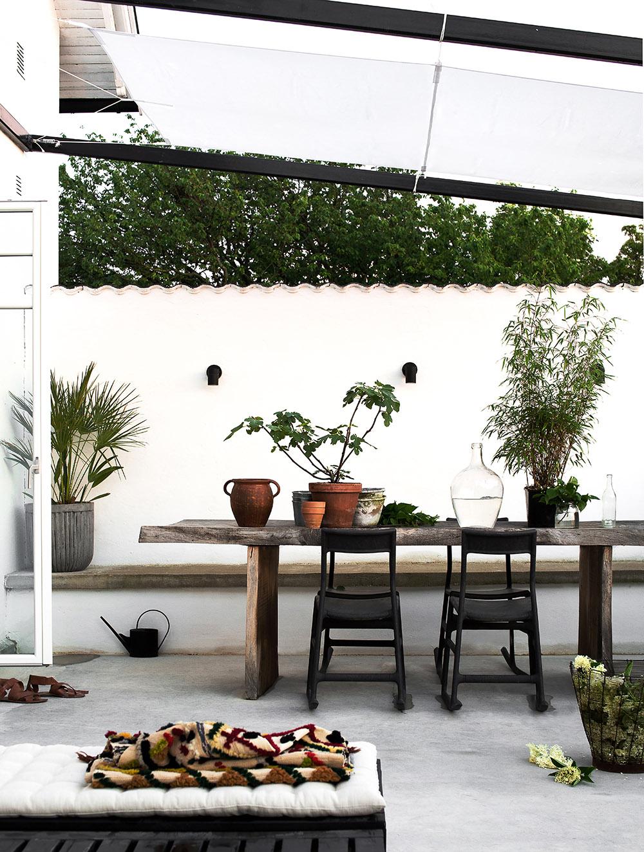 terraza decorada con mesa de madera y plantas
