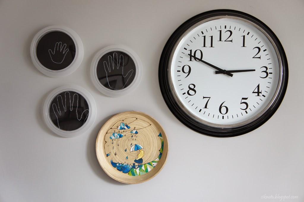 reloj en una pared blanca y huellas de niños
