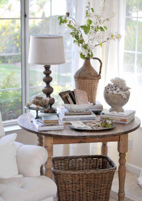 mesa con una lampara, varios libros, jarrones, plantas