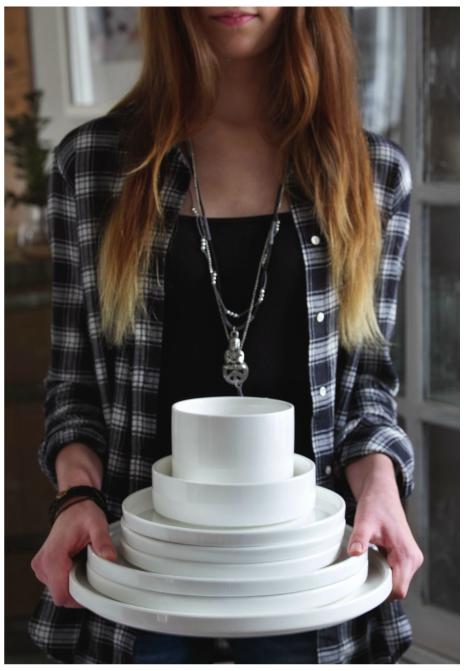 chica llevando unos tazones y platos blancos
