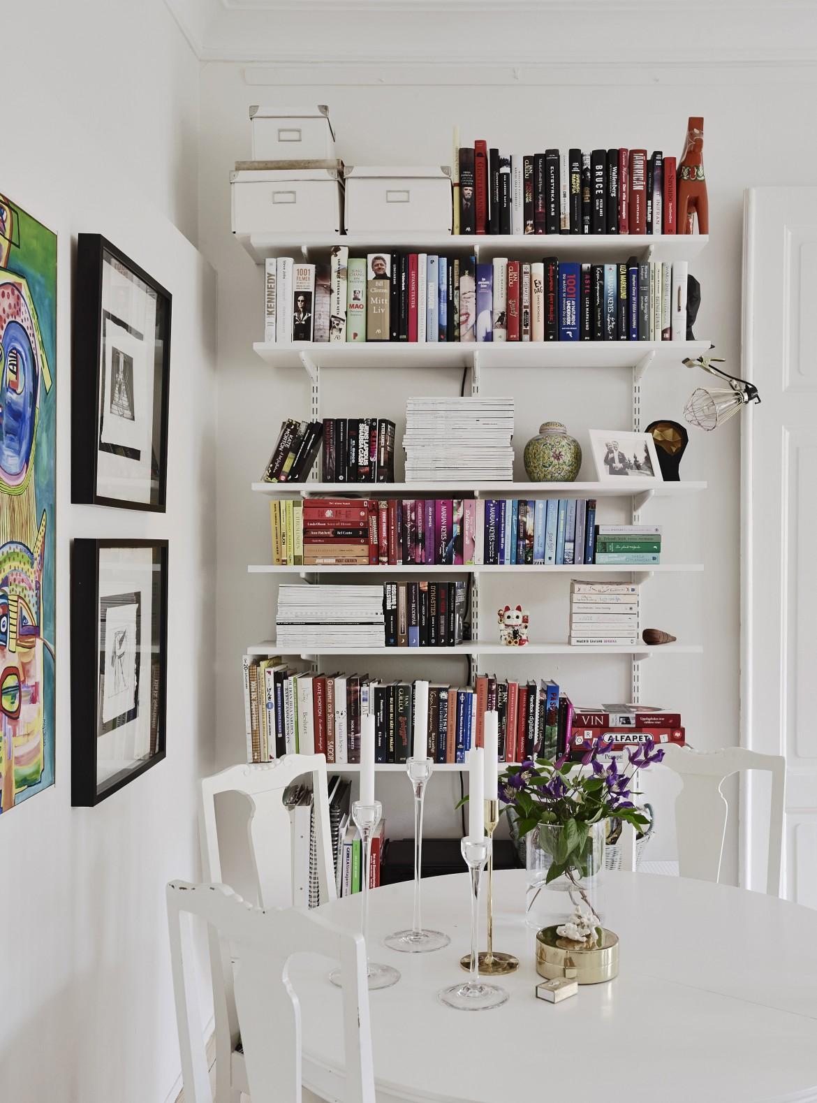 mesa y sillas al lado de una estantería con libros